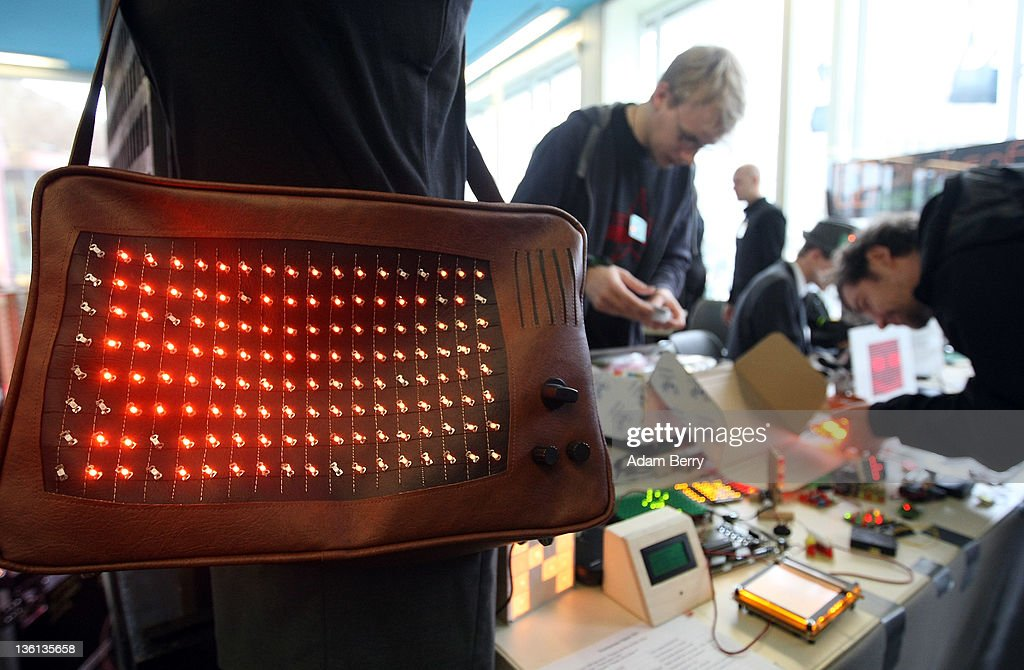 Participants in the BlinkenArea project work behind a handbag shaped like a vintage television with an animated panel of LED lights on the first day of the 28th Chaos Communication Congress (28C3) - Behind Enemy Lines computer hacker conference on December 27, 2011 in Berlin, Germany. The Chaos Computer Club is Europe's biggest network of computer hackers and its annual congress draws up to 3,000 participants.