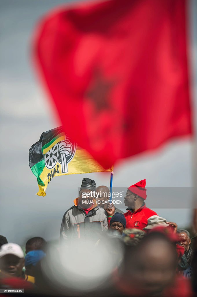 Participants in the congress of South African Trade Unions (COSATU) cheer as they attend the May Day rally at Mamelodi's Moreleta park on May 1, 2016 in Pretoria. Secretary General Sdumo Dlamini, South African Communist Party leader Blade Nzimande and South African President Jacob Zuma took part in the rally. / AFP / MUJAHID