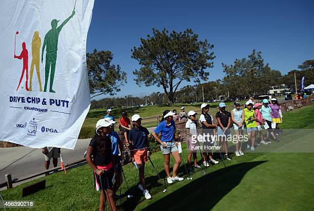 Participants in the girls 1213 division wait to participate in the putting section of the competition during a regional round of the Drive Chip and...