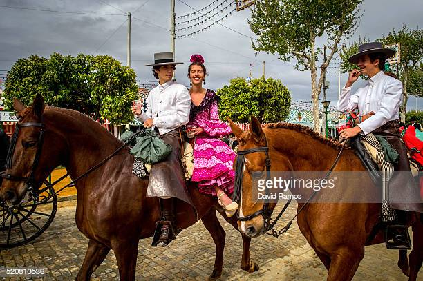 Participants in traditional dress ride on horseback as they enjoy the atmosphere at the Feria de Abril on April 12 2016 in Seville Spain The Feria de...