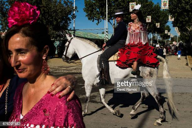 Participants in traditional dress ride on horseback as they enjoy the atmosphere at the Feria de Abril on May 1 2017 in Seville Spain The Feria de...