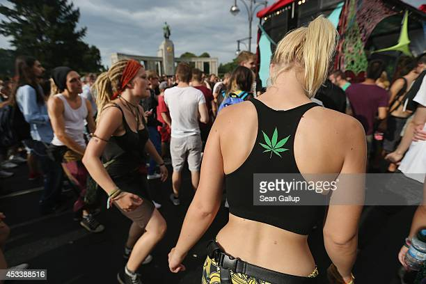 Participants including one with a marijuana leaf emblem on her back dance at the annual Hemp Parade on August 9 2014 in Berlin Germany Supporters of...