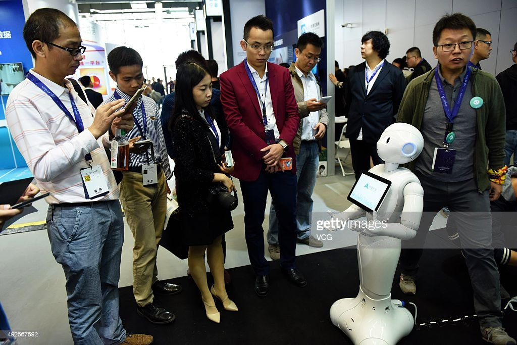 Participants interact with personal robot 'Pepper', a human-like robot on the 2015 Computing Conference on October 14, 2015 in Hangzhou, Zhejiang Province of China. Pepper is a personal robot that can gauge human emotions for more natural human/robot interaction. It is joint invested by Alibaba Group, SoftBank Group Corp. and Foxconn Technology Group, and developed by SoftBank Robotics Holdings Corp., under SoftBank Group Corp..