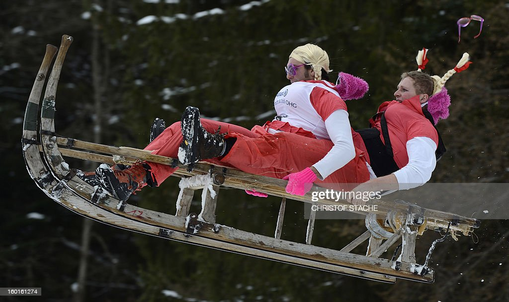 Participants jump with their sled during the traditional Schnablerrennen sledge race in a valley near the Bavarian village Gaissach, southern Germany, on January 27, 2013. More than 70 teams took part in the traditional event. AFP PHOTO / CHRISTOF STACHE