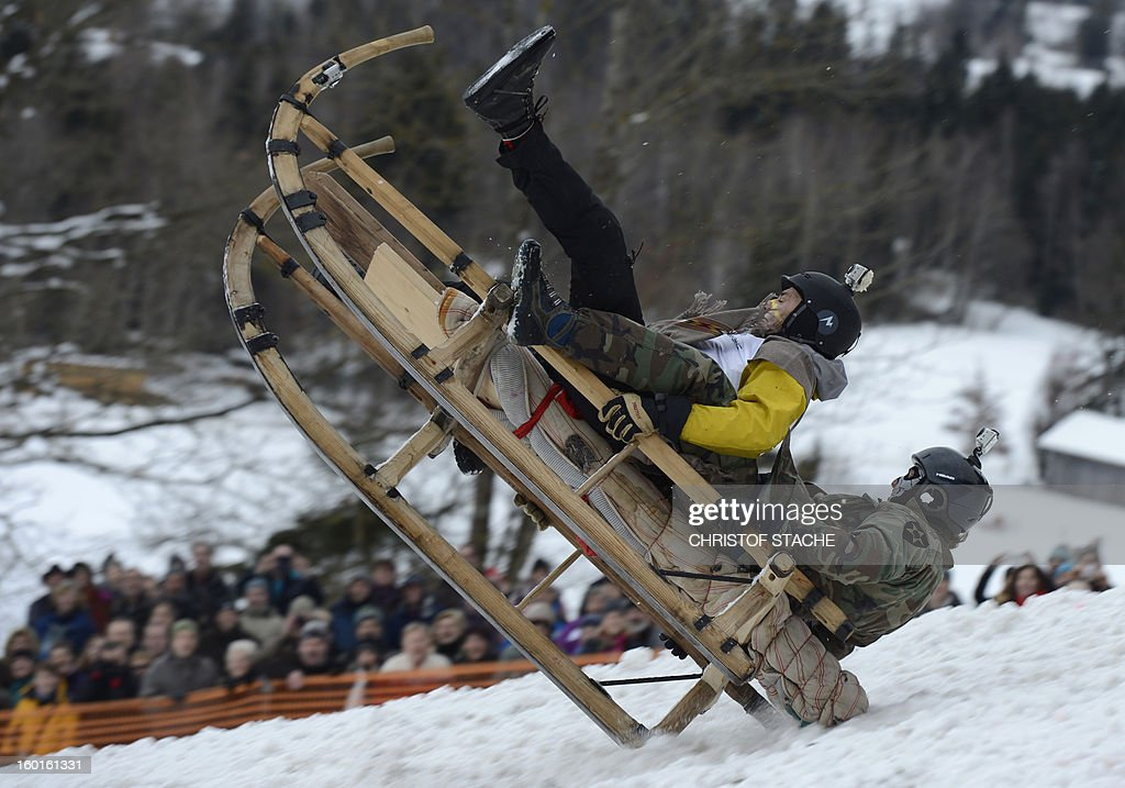 Participants land with their sled during the traditional Schnablerrennen sledge race in a valley near the Bavarian village Gaissach, southern Germany, on January 27, 2013. More than 70 teams took part in the traditional event. AFP PHOTO / CHRISTOF STACHE