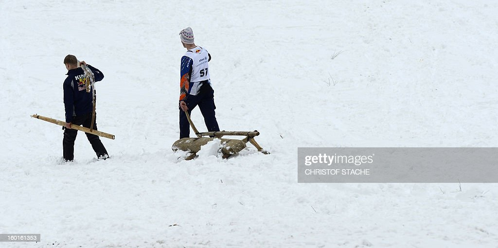 Participants leave the arena with their broken sled during the traditional Schnablerrennen sledge race in a valley near the Bavarian village Gaissach, southern Germany, on January 27, 2013. More than 70 teams took part in the traditional event. AFP PHOTO / CHRISTOF STACHE