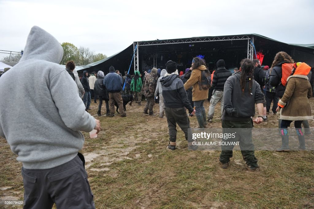 Participants listen to music during the 'Frenchtek 23' Teknival music festival near Salbris, central France on April 30, 2016. / AFP / GUILLAUME