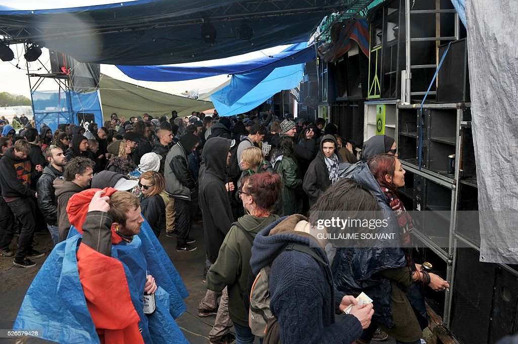 Participants listen to music under a tent during the 'Frenchtek 23' Teknival music festival near Salbris, central France on April 30, 2016. / AFP / GUILLAUME