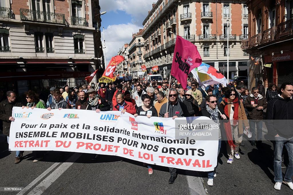 Participants march with a banner as they protest against the government's proposed labour law reforms during the traditional May Day demonstration in Toulouse, southern France, on May 1, 2016. / AFP / REMY