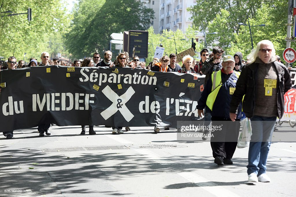 Participants march with a banner reading 'Separation of MEDEF (France's largest employer federation) and state' as they protest against the government's proposed labour law reforms during the traditional May Day demonstration in Toulouse, southern France, on May 1, 2016. / AFP / REMY