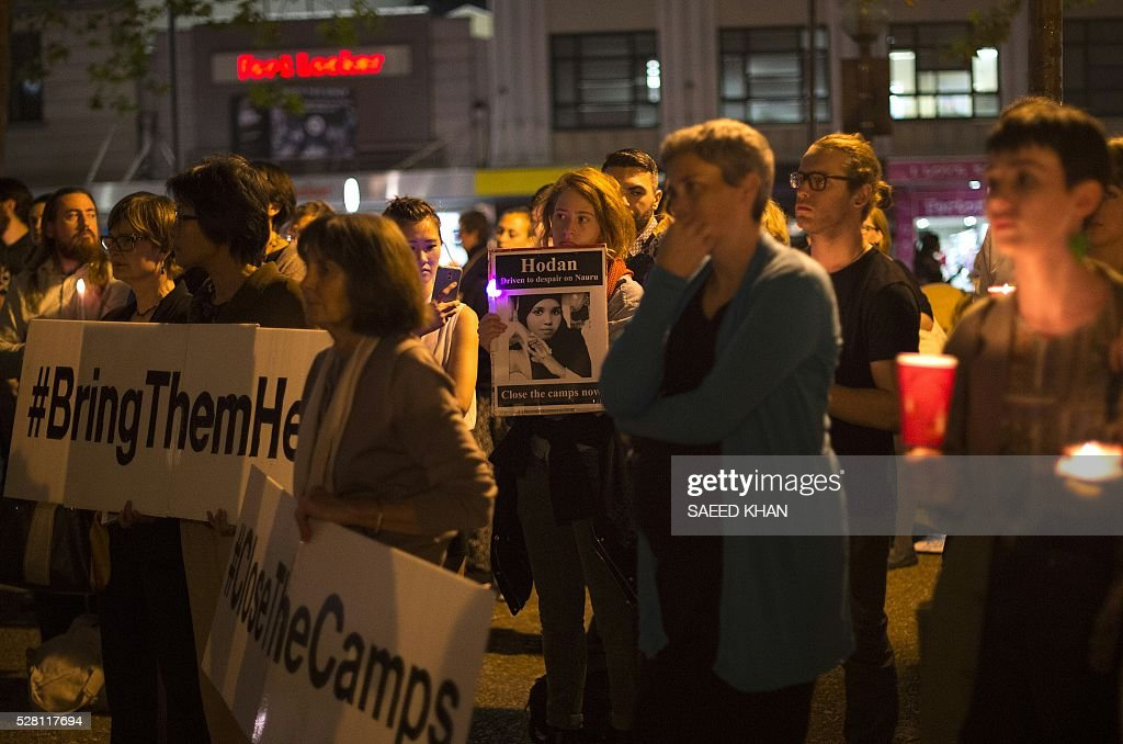Participants observe a minute silence during a candle light vigil for two refugees, a Somali woman and an Iranian man who set themselves on fire on the remote Pacific island of Nauru, during a candle light vigil in Sydney on May 4, 2016. More than 750 asylum-seekers held in a Papua New Guinea detention camp launched legal action on May 4, 2016 to be moved to Australia after a court in the Pacific nation found the centre unconstitutional. / AFP / SAEED