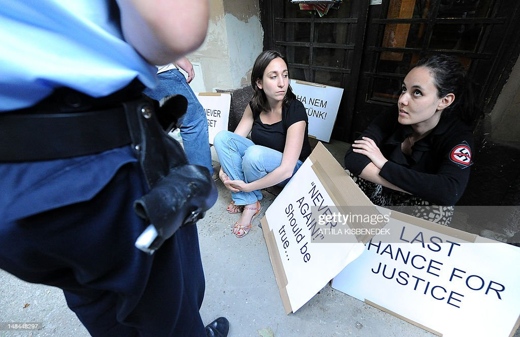 Participants of a demonstration called by the European Union of Jewish Students sit with their placards bearing protest slogans as a local police officials control their ID in front of Laszlo Csatary's hideaway building, only few kilometers from his home in Budapest on July 16, 2012 after their non-reported demonstration against Csatary. The demonstration was called after a Hungarian prosecutor said that investigating an aged Nazi war criminal found alive and well in Budapest was problematic because the events took place so long ago and in a different country. A probe into Laszlo Csatary, 97, began in September after information was received from the Nazi-hunting Simon Wiesenthal Center, which ranks him number one on their wanted list, the public prosecutors' office said.