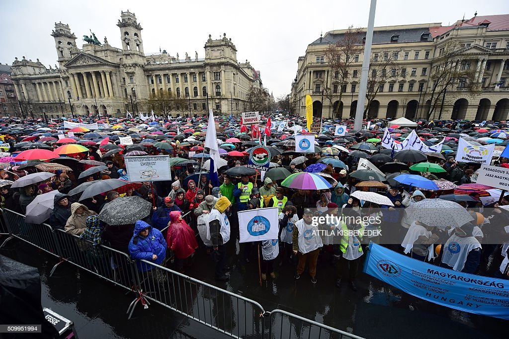 Participants of a demonstration for teachers, parents and their sympathizers hold their banners in front of the parliament building in Budapest downtown on February 13, 2016 during their anti-government demonstration to protest against proposed education reforms of the Orban's government. / AFP / ATTILA KISBENEDEK