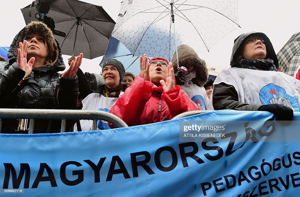 Participants of a demonstration for teachers, parents and their sympathizers hold banners and umbrellas in front of the parliament building in Budapest downtown on February 13, 2016 during their anti-government demonstration to protest against the education policy of the Orban's government. / AFP / ATTILA KISBENEDEK