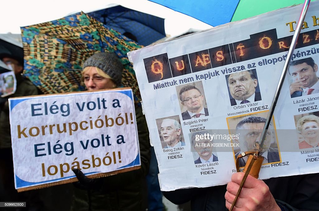 Participants of a demonstration for teachers, parents and their sympathizers hold signs reading 'We don't get our stolen money back, because of them' and depicting leaders of the governing FIDESZ party (R) and 'Enough for corruption, enough for theft' in front of the parliament building in Budapest downtown on February 13, 2016 during their anti-government demonstration to protest against the education policy of the Orban's government. / AFP / ATTILA KISBENEDEK