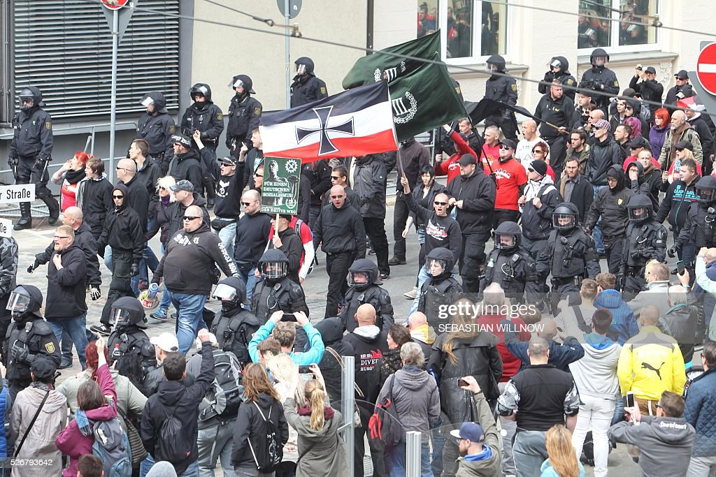 Participants of a farright demonstration walk in Plauen, eastern Germany, accompanied by police forces, on May 1, 2016. / AFP / dpa / Sebastian Willnow / Germany OUT