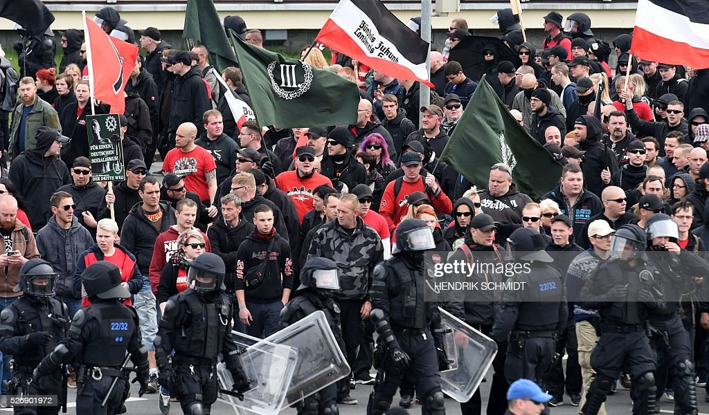 Participants of a farright demonstration walk in Plauen, eastern Germany, accompanied by police forces, on May 1, 2016. / AFP / dpa / Hendrik Schmidt / Germany OUT