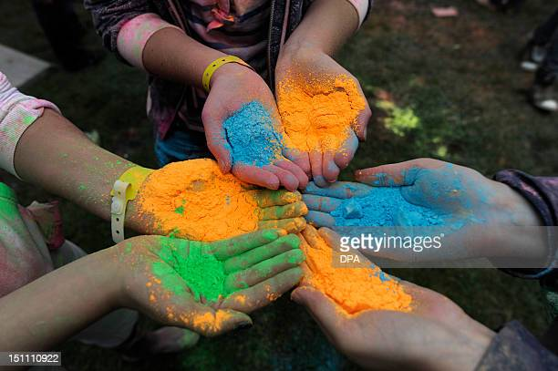 Participants of a Holi Open Air festival hold in their hands color pigments in the Wedemark region near Hanover central Germany on September 1 2012...