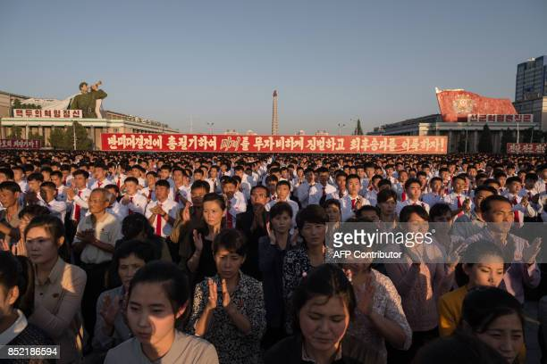 Participants of a mass rally gather before a banner reading 'let us smash down the US imperialists and be victorious rising to the antiAmerica...