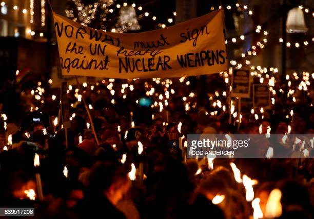 Participants of a torchlight procession organized by the Norwegian Peace Council hold a banner reading 'Norway must sign the UN treaty against...