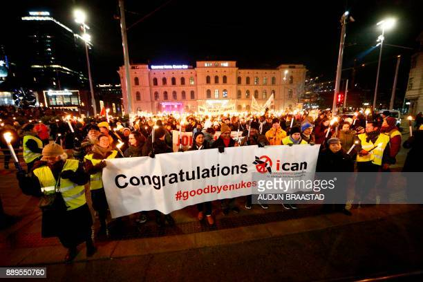 Participants of a torchlight procession organized by the Norwegian Peace Council hold a banner reading 'Congratulations ICAN' in honour of the 2017...