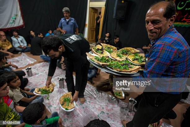 Participants of Tazieh ritual theater of the day of Ashura eat beryun traditional Iranian dish made from lamb cutlet and served with nanetaftun bread...