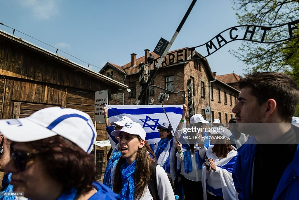 Participants of the annual 'March of the Living' pass the main gate of the former Nazi death camp in Oswiecim (Auschwitz), Poland, on May 5, 2016. Thousands of young Jews from 40 nations marched alongside a handful of Holocaust survivors and Polish teenagers in homage to the victims of the former Auschwitz-Birkenau WWII death camp in southern Poland. / AFP / WOJTEK