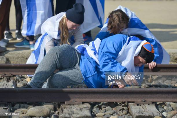 Participants of the annual March of the Living place little rocks on the rails in the former German Nazi Death Camp AuschwitzBirkenau Jewish people...