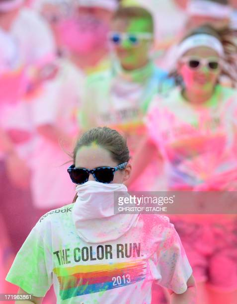 Participants of the color run wear sunglasses as they get a colored powder shower at the pink zone during the event in Munich southern Germany on...