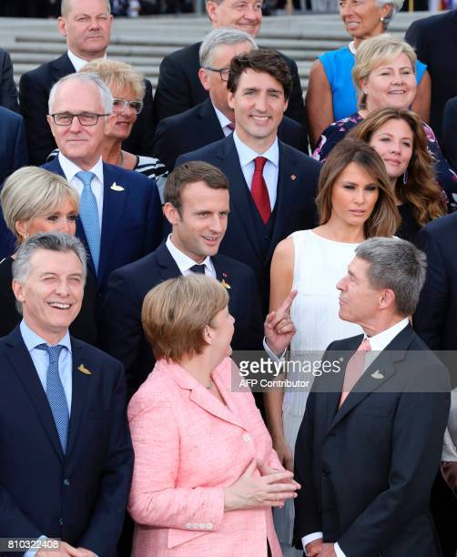 Participants of the G20 summit and their spouses pose for a family photo as French President Emmanuel Macron jokes with Joachim Sauer the husband of...