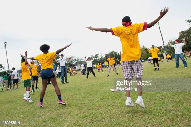 Participants of the Laureus Academy Youth Run NOLA initiative warm up doing jumping jacks on September 30 2013 in New Orleans Louisiana