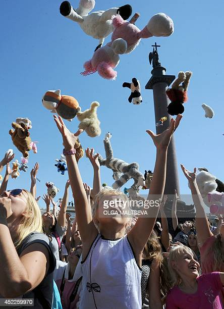 Participants of the Soft Dolls Parade throw up toys during a flash mob event at the Dvortsovaya Square in St Petersburg on July 16 2014 AFP PHOTO /...