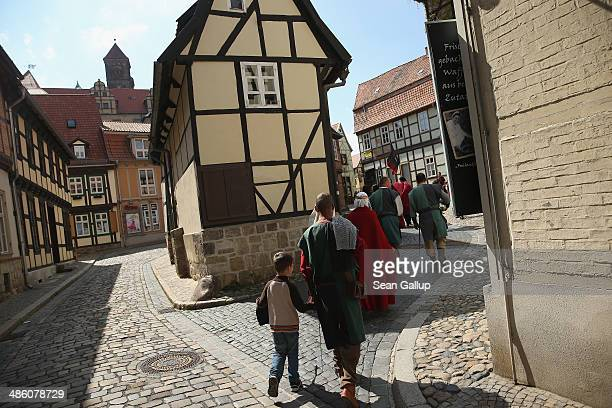 Participants on their way to a gathering of Medieval enthusiasts walk among halftimbered houses on April 20 2014 in Quedlinburg Germany Quedlinburg...