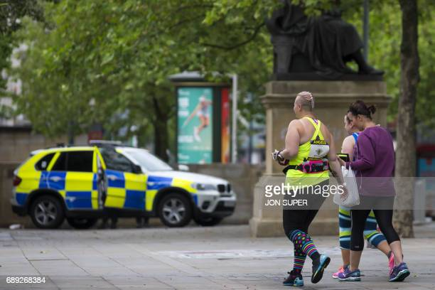 Participants pass a police vechile on their way to the start of the Great Manchester Run in Manchester on May 28 2017 Britain police have released...