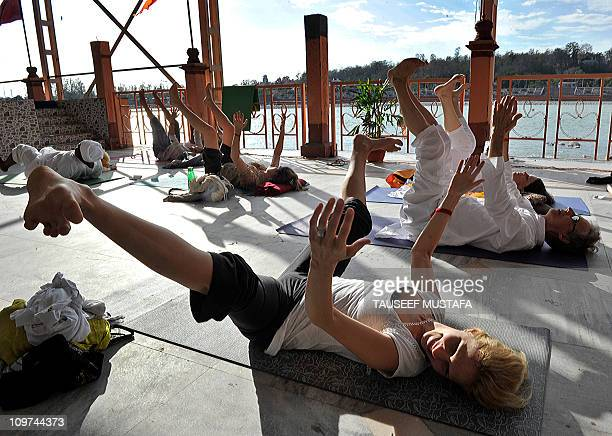 Participants perform yoga exercises during the international Yoga festival at the Parmarth Niketam Ashram in Rishikesh on March 3 2011 The Himalayan...