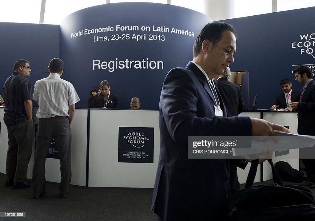 "Participants pick up their press kits in Lima on April 23, 2013, on the eve of the inauguration of the World Economic Forum on Latin America. Under the slogan ""Delivering Growth, Strengthening Societies"", regional and global leaders will discuss on April 23-24 the opportunities and challenges that lie ahead to achieve the region's full potential."