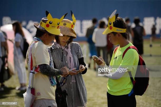 Participants play Nintendo Co's Pokemon Go augmentedreality game developed by Niantic Inc on their smartphones during a Pikachu Outbreak event...