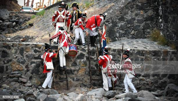 Participants playing the role of British soldiers climb a wall as they take part in a historical reenactment of a battle between Spanish and British...
