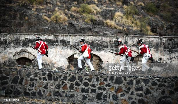 Participants playing the role of British soldiers walk on a wall as they take part in a historical reenactment of a battle between Spanish and...