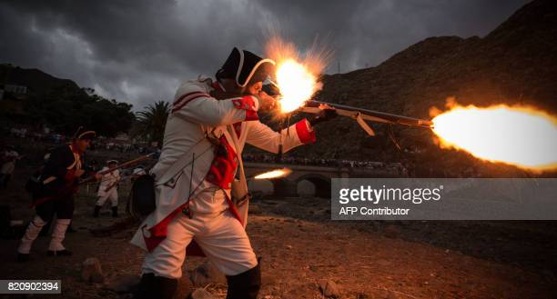Participants playing the role of Spanish soldiers shoot their guns as they take part in a historical reenactment of a battle between Spanish and...