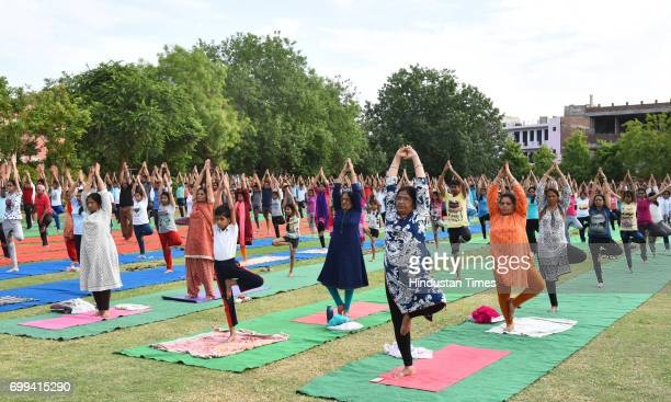 Participants practice an Yogic Posture during the Mass Yoga Practice organised on International Yoga Day at National Institute of Ayurveda on June 21...