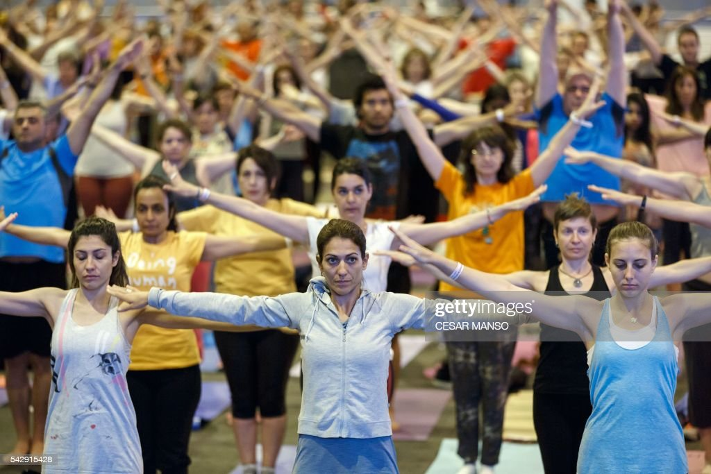 Participants practice yoga during the Stomp Yoga Masterclass part of the 17th edition of IIFA Awards (International Indian Film Academy Awards) in Madrid on June 24, 2016. The IIFA Awards are presented annually by the International Indian Film Academy to honour both artistic and technical excellence of professionals in Bollywood, the Hindi language film industry. / AFP / CESAR