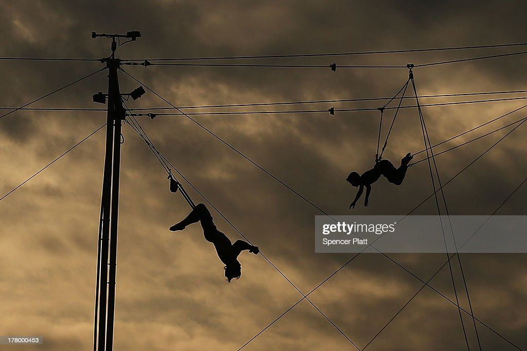 Participants practices on a trapeze at the Trapeze School of New York on the West Side of Manhattan beside the Hudson River on August 26, 2013 in New York City. Over recent years, much of the West Side of Manhattan along the river has been re-developed into parks, restaurants and walking paths.
