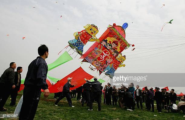 Participants prepare and fly traditional kites some featuring the 2008 Beijing Olympics logo at the Weifang Kite Festival on April 21 2006 in Weifang...