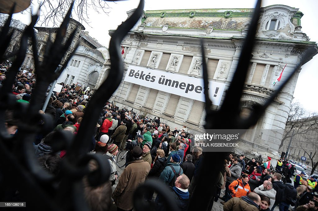 Participants protest against the new Hungarian Constitution during an anti-government demonstration in front of the headquarters of the governor FIDESZ in Budapest on March 30, 2013. The fourth modification of the basic law will be come into force on April 1. The banner reads- 'Peaceful holidays (Easter). AFP PHOTO / ATTILA KISBENEDEK