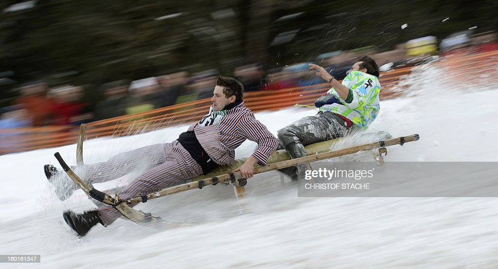 Participants race with their sled during the traditional Schnablerrennen sledge race in a valley near the Bavarian village Gaissach, southern Germany, on January 27, 2013. More than 70 teams took part in the traditional event. AFP PHOTO / CHRISTOF STACHE