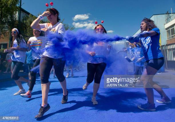Participants react as volunteers launch colourful powder at them during 'The Color Run' around Wembley Stadium in London on June 7 2015 The Color Run...