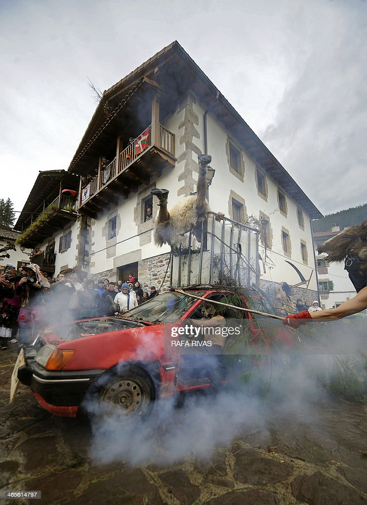 Participants rev up a car during the ancient carnival of Zubieta, in the northern Spanish province of Navarra province, on January 28, 2014. The yearly three day festivities, revolving mainly around agriculture and principally sheep hearding, run on the last Sunday, Monday and Tuesday of January where Navarra Valley locals from three villages dress up and participate in a variety of activites as they perform a pilgrimage through each village.