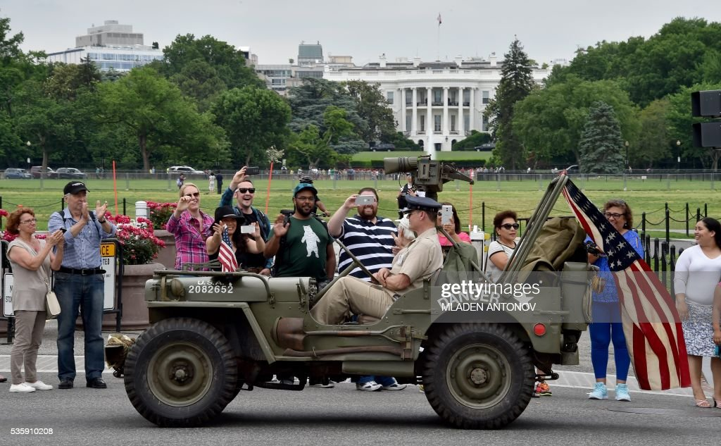 Participants ride a WWII Jeep in front of the White House during the Memorial Day Parade on Constitution Avenue in Washington DC on May 30, 2016. / AFP / MLADEN