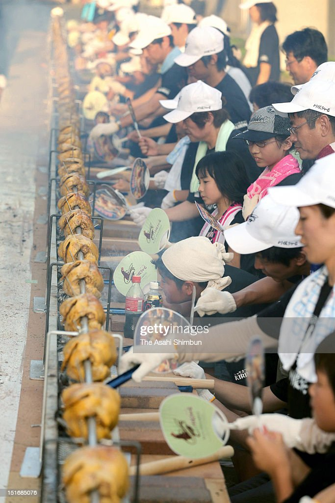 Participants roast Kawamata gamecock standing in line, using a 35-meter-long stainless skewer in challenge for the world longest row of roasted chicken on September 1, 2012 in Kawamata, Fukushima, Japan.